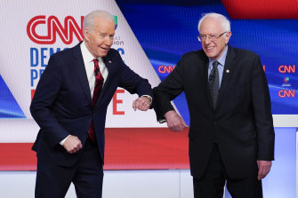 Former Vice President Joe Biden, left, and Senator Bernie Sanders greet each other before they participate in a Democratic presidential primary debate in Washington.