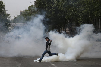 A protester kicks a tear gas canister launched by police during a protest in Santiago, Chile, on Saturday.