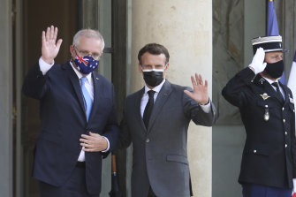 French President Emmanuel Macron, center, and Australia's Prime Minister Scott Morrison wave to reporters before a working dinner at the Elysee Palace in Paris, Tuesday, June 15, 2021.