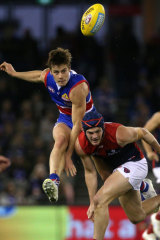 Dynamic: Josh Dunkley kicks on under pressure from Melbourne's Angus Brayshaw.