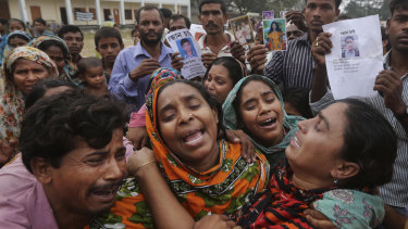 Bangladeshi relatives of garment worker Mohammed Abdullah cry as they as they arrive to collect his body at a makeshift morgue in a schoolyard near a building that collapsed in Savar, near Dhaka, Bangladesh in 2013.