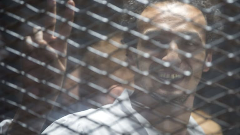 Mahmoud Abu Zaid, a photojournalist known as Shawkan smiles inside a cage in an Egyptian Court in Cairo, Egypt, on Saturday.