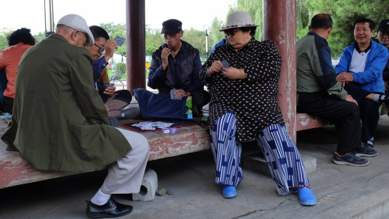 Tumen residents play cards in a park on the border with North Korea on Friday.