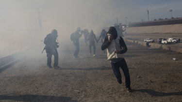Migrants run from tear gas launched by US agents, amid photojournalists covering the Mexico-US border.