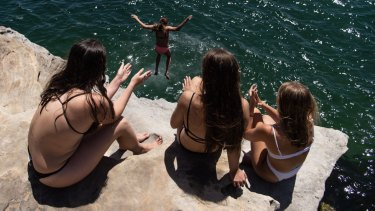Swimmers jump off the rocks at Neilson Park to beat the heat.