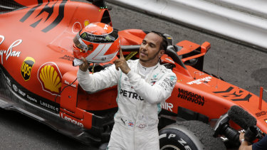 Mercedes driver Lewis Hamilton holds his red helmet to tribute Niki Lauda after he won the Monaco Grand Prix.