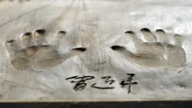 Xi Jinping's handprints are imprinted on a wet clay slab during the BRICS Summit in Johannesburg.