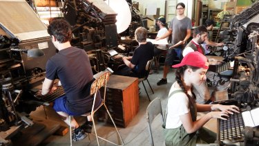 The museum's 'newspaper composing room' with people posing as Linotype as operators and (standing) a copy boy, handing out the  text the typesetters will compose.