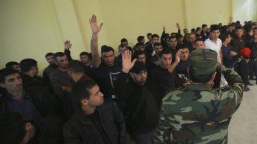 Azerbaijani men gather in a military commissariat to join the army in Tartar region, Azerbaijan.