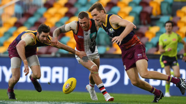 Hot pill: St Kilda's Tim Membrey struggles to hold off a pair of Lions.