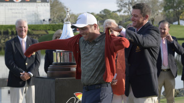 Triumph: Sam Saunders, Arnold Palmer's grandson, helps Francesco Molinari, put on a tournament sweater after winning the Arnold Palmer Invitational.