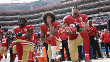 Colin Kaepernick (centre) kneeling in protest.