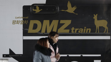 "Visitors walk past a train carrying letters ""Peace train"" and ""DMZ train"" at Imjingang Station in Paju."