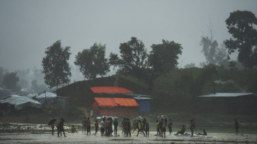Rohingya children play in a downpour at the world's largest refugee camp at Cox's Bazar last year.