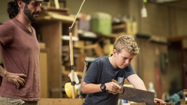Woodwork enthusiast Lachlan Mayne, 13, under the supervision of expert Luke Mitchell  at the co-operative.