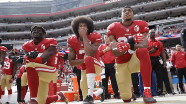 Colin Kaepernick (centre), then the quarterback of the San Francisco 49ers, takes a knee during the national anthem with teammates Eli Harold (left) and Eric Reid at an NFL game in October 2016.