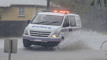 A police car drives through floodwater in south Townsville.