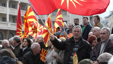 People wave the old and present national flag in a protest against the change of the country's constitutional name, in downtown Skopje, in November 2018.