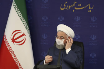 President Hassan Rouhani adjusts his face mask in Tehran during a meeting on the nation's fight against COVID-19.