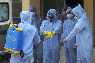 Municipal workers in protective suits sanitise themselves after cremating a COVID-19 victim in Mumbai on Thursday.
