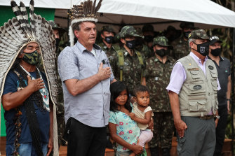 Brazilian President Jair Bolsonaro, second from left, sings the national anthem at a ceremony to open the new bridge leading to an area wheremajor reserves of niobium have been found.
