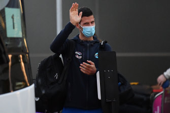 Novak Djokovic waves as he arrives at Adelaide Airport on Thursday.