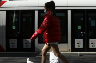Pedestrians wear face masks to prevent the spread of coronavirus at Town Hall in Sydney's CBD.