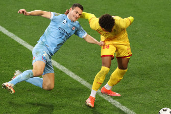 Curtis Good of Melbourne City and Kusini Yengi of Adelaide United compete for the ball.