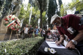 People pay homage at the grave of  Andrea Camilleri in Rome on Thursday.