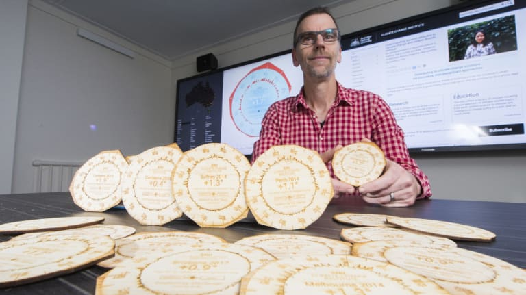 Dr Geoff Hinchcliffe from the ANU School of Art and Design with coasters made from laser cut wood showing the climate shift for an Australian city.