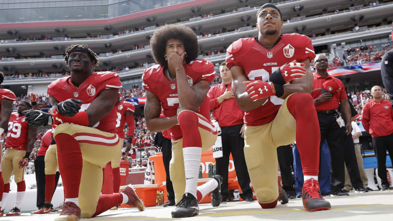Prominence: Colin Kaepernick (centre) hasn't found a new team, but remains at the forefront of the anthem issue.