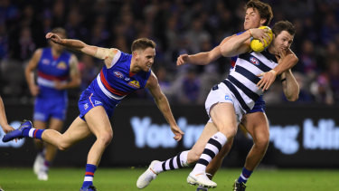 Caught: Geelong's Patrick Dangerfield gets tied up on a tough night against the Bulldogs.