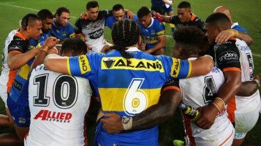 Coming together: Players from the Tigers and Eels in a post-game prayer circle.