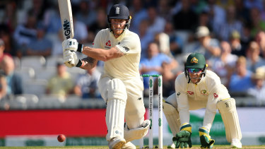Ben Stokes of England reverse sweeps watched on by Tim Paine.