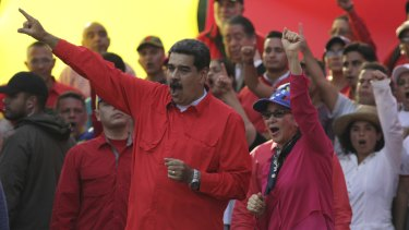 Venezuelan leader Nicolas Maduro, centre left, and his wife Cilia Flores, centre right, wave at supporters during a rally in Caracas on May 1.