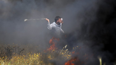 A Palestinian protester slings stones towards Israeli soldiers on Friday.