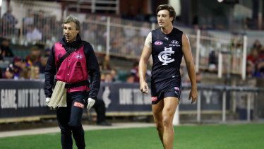 Hobbling off: Carlton's Caleb Marchbank leaves the field after suffering an injury.