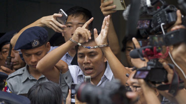 Reuters journalist Kyaw Soe Oo is escorted by police as they leave the court on Monday. He faces seven years in jail.
