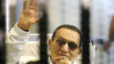 Hosni Mubarak waves to his supporters from behind bars as he attends a hearing in his retrial on appeal in Cairo on April 13, 2013.