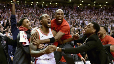 Dagger: Kawhi Leonard is mobbed by teammates after his incredible shot to clinch the series against Philadelphia.