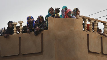 Sudanese stand on their roof top house, as they watch the arrival of General Abdel-Fattah Burhan, head of the military council, during a military-backed rally, in Omdurman district, west of Khartoum, Sudan on Saturday.