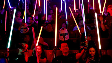 Epic fandom: Star Wars fans raise their lightsabers before the starts of Star Wars: The Last Jedi movie.