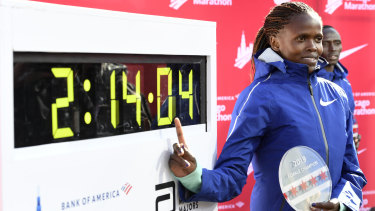 Brigid Kosgei of Kenya poses with her time after winning the Chicago Marathon while setting a world record.
