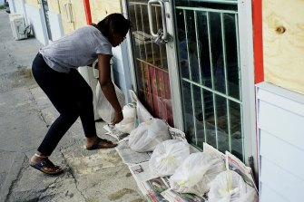 Yolande Rolle sandbags her shop as she prepares for the arrival of Hurricane Dorian in Freeport on Grand Bahama on Sunday.