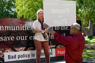 A protester holds a 'Pause the Plan' sign in front of Sussan Ley at a rally in Albury in April.