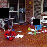 The five photos show William and another child sitting on a veranda drawing.