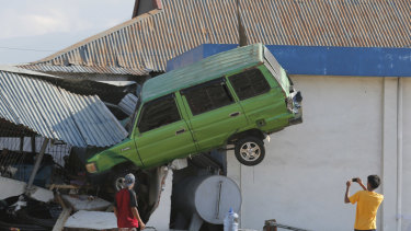 A man takes a photo of a car lifted into the air by the tsunami at Talise beach in Palu,