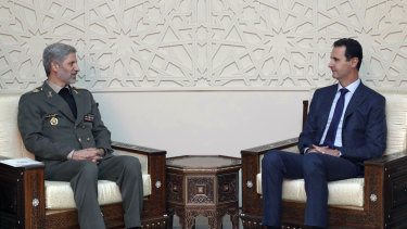Syrian president Bashar al-Assad, right, meets with Iran's Defence minister Amir Hatami, in Damascus, Syria, on Sunday.