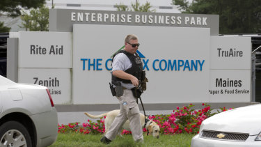 A sniffer dog searches the industrial complex where the shooting occurred.