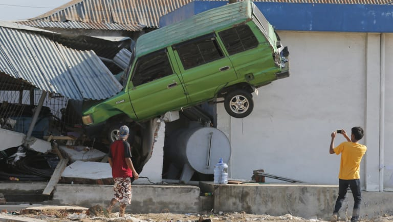 A man takes a photo of a car lifted into the air with his mobile phone following a massive earthquake and tsunami at Talise beach in Palu,